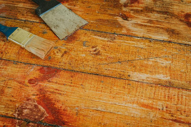 Wooden floor renovation - Scrape tool and brush placed on floor with paint scraped.  stock image