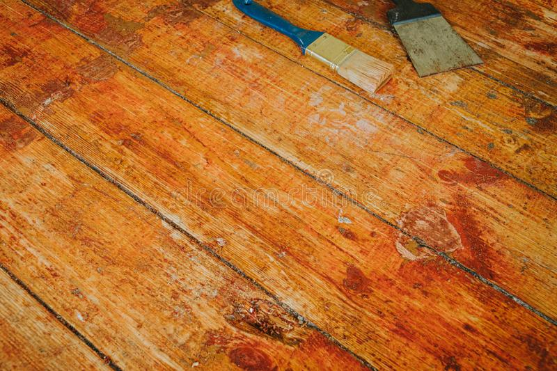 Wooden floor renovation - Scrape tool and brush placed on floor with paint scraped.  royalty free stock photography