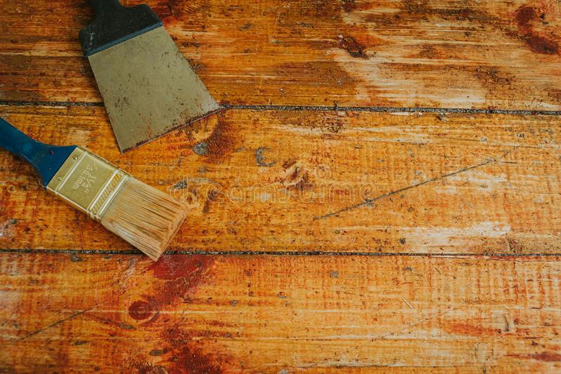 Wooden floor renovation - Scrape tool and brush placed on floor with paint scraped.  stock photo