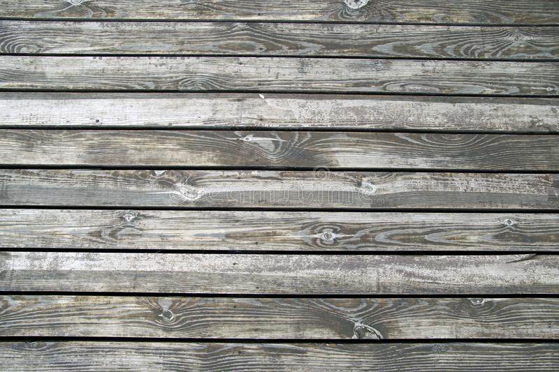 Wooden floors of the terrace on the river bank. Texture of wet unpainted wood royalty free stock photos