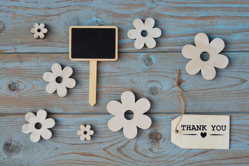 Wooden flowers, black chalk board and thank you label on a blue grey knotted old wooden background with empty space layout stock images