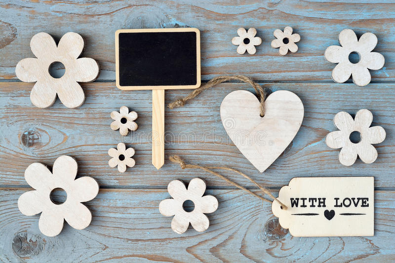 Wooden flowers, heart, black chalk board and with love label on a blue grey knotted old wooden background with empty space layout stock image