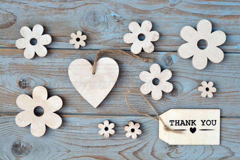 Wooden flowers, heart, black chalk board and thank you label on a blue grey knotted old wooden background with empty space layout stock photo