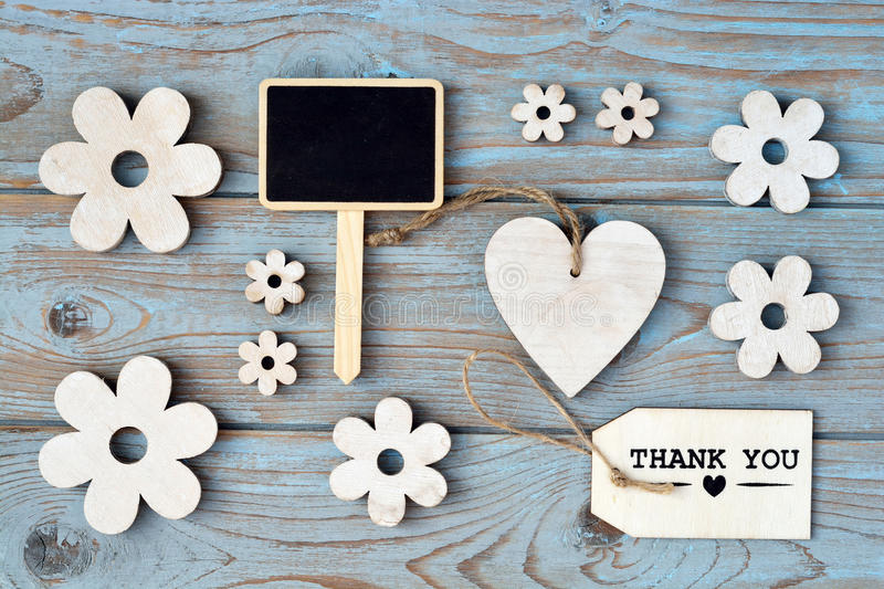 Wooden flowers, heart, black chalk board and thank you label on a blue grey knotted old wooden background with empty space layout royalty free stock photos