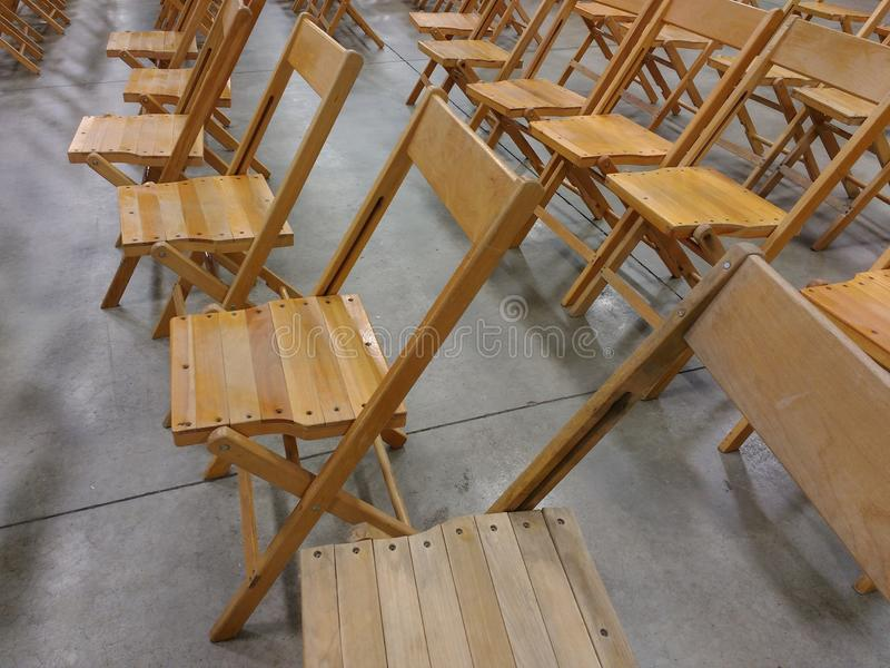 Wooden Folding Chairs. Rows of wood chairs are arranged in anticipation of an event royalty free stock image