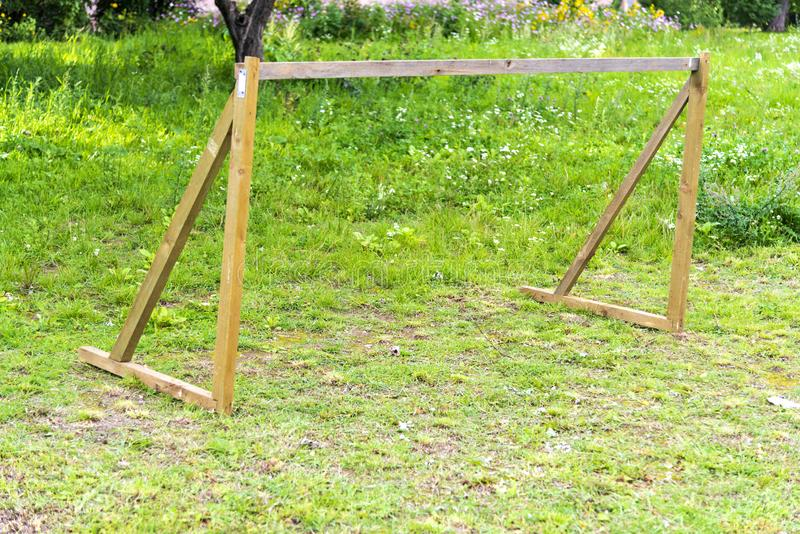 Wooden football goal without a net on a green field. Make a football goal for children in the courtyard of the house.  royalty free stock photography