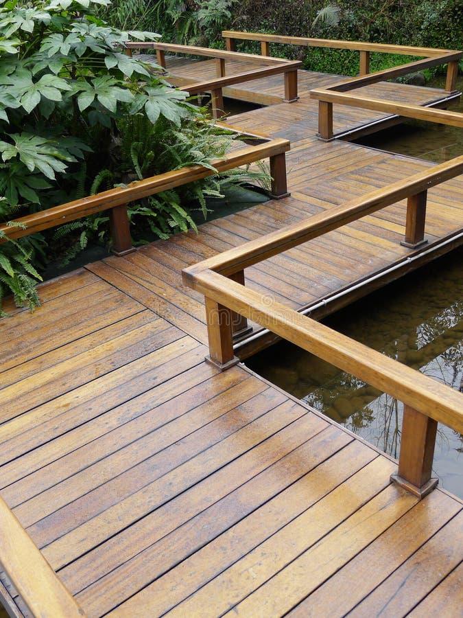 Wooden footbridge. Zigzag style wooden footbridge in the park stock photography