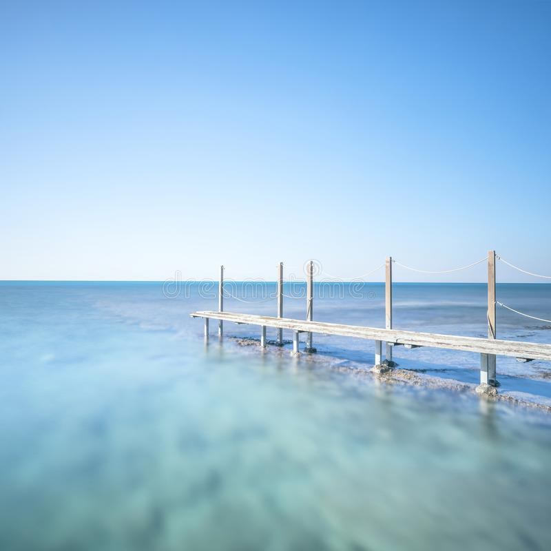 Wooden footbridge or catwalk and banister on ocean water. Long e royalty free stock image