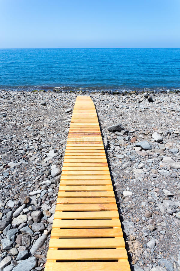 Wooden footpath on beach leading to portuguese sea stock image