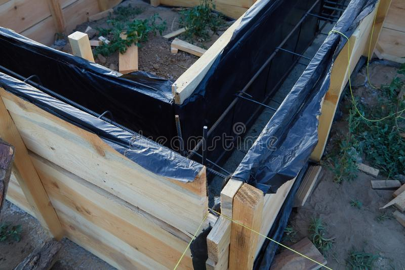 Wooden formwork concrete strip foundation for a cottage. Foundation site of new house, building, details and reinforcements with steel bars and wire rod royalty free stock photography