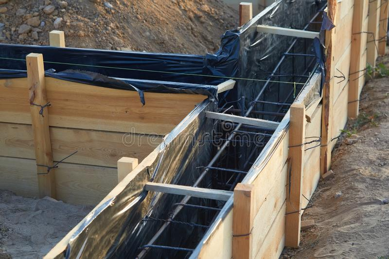 Wooden formwork concrete strip foundation for a cottage. Foundation site of new house, building, details and reinforcements with steel bars and wire rod stock photos