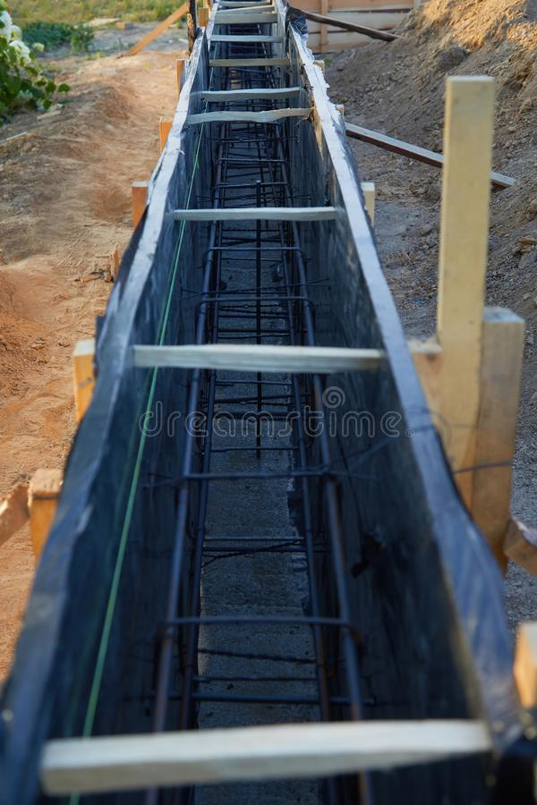Wooden formwork concrete strip foundation for a cottage. Foundation site of new house, building, details and reinforcements with steel bars and wire rod royalty free stock image
