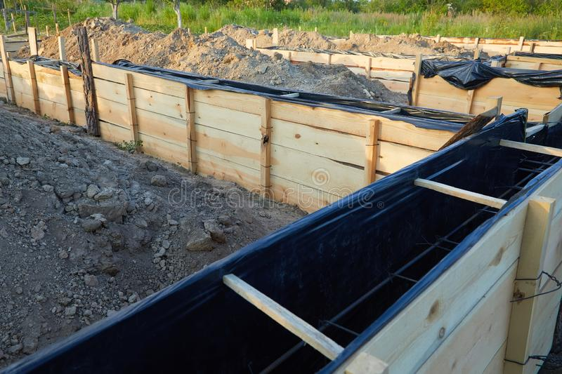 Wooden formwork concrete strip foundation for a cottage. Foundation site of new house, building, details and reinforcements with steel bars and wire rod royalty free stock photo