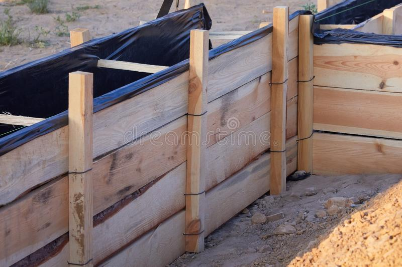 Wooden formwork concrete strip foundation for a cottage. Foundation site of new house, building, details and reinforcements with steel bars and wire rod royalty free stock photos
