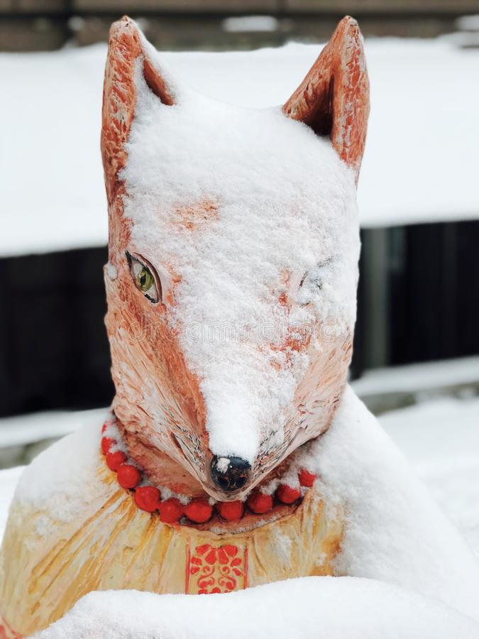 A wooden fox wears a stylish necklace and a coat of white snow. One eye is open on a trusty and sly fox. The fox wears Ukrainian folk garb royalty free stock images