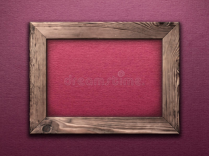 Wooden Frame. Old wooden frame empty inside on purple wall royalty free stock image