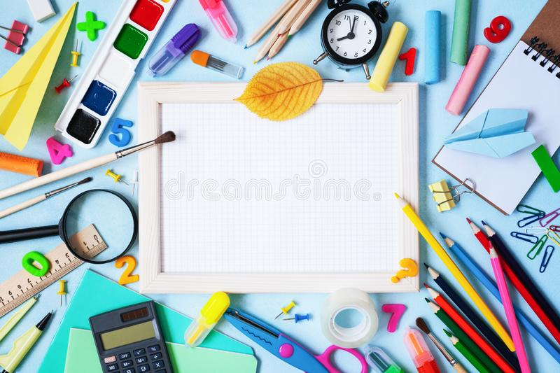 Wooden frame, alarm clock, different stationery and colorful supplies on blue background. Back to school concept. Top view stock photography