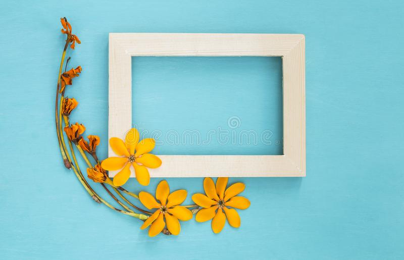 Wooden frame decorate with yellow flower. On blue background stock photos