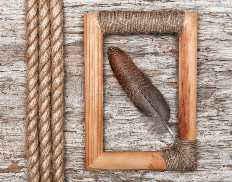 Wooden frame, feather and rope on the old wood stock images