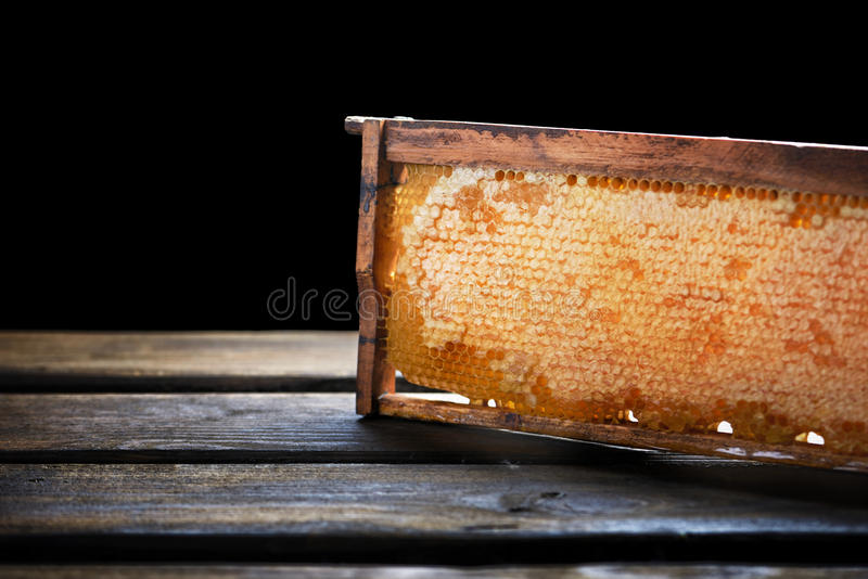 Wooden frame with honeycomb full of honey, on black. Wooden frame with honeycomb full of honey, on wooden pallet, on black stock image