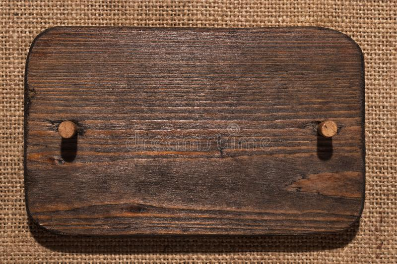 Wooden frame made of dark wood with wooden gag lies on burlap. With a place for your text royalty free stock photography