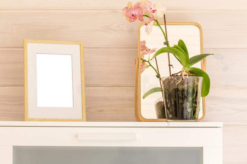 Wooden frame mock up and phalaenopsis orchid on a white chest in a bedroom of a wooden house with white trim. stock photography