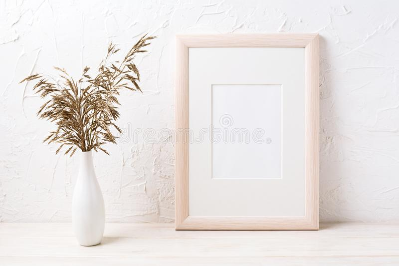 Wooden frame mockup with dried grass. Wooden frame mockup with decorative dried grass. Empty frame mock up for presentation design. Template framing for modern royalty free stock images