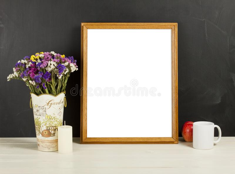 Wooden frame mockup with field flowers in vase, apple, mug and c. Andle. Empty frame mock up for presentation design. Template framing for modern art royalty free stock photography