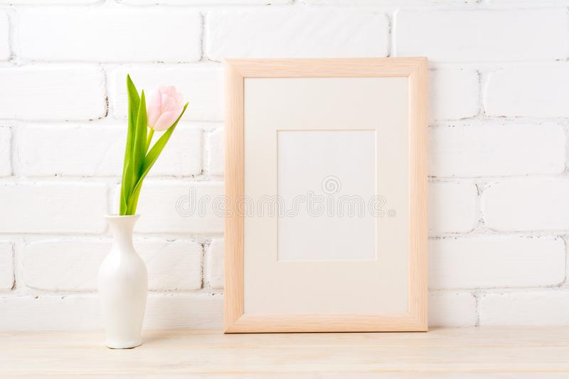 Wooden frame mockup with pale pink tulip in vase. Wooden frame mockup with soft pink tulip in elegant vase near white painted brick wall. Empty frame mock up for royalty free stock photo
