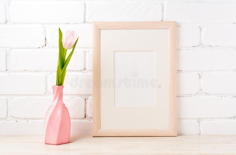 Wooden frame mockup with pink tulip in swirled vase royalty free stock images
