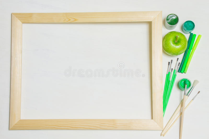 Wooden frame with paintbrushes and green apple royalty free stock photography