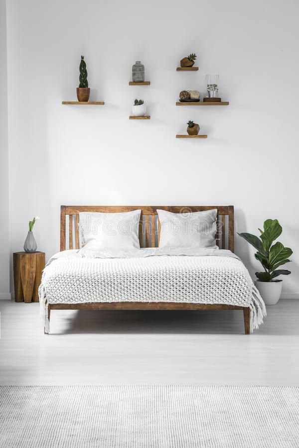 Wooden framed double bed with two pillows and a blanket, and small shelves above in a white bedroom interior. Real photo. royalty free stock image