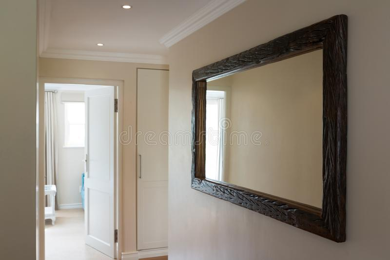 Wooden framed mirror on white wall stock photo
