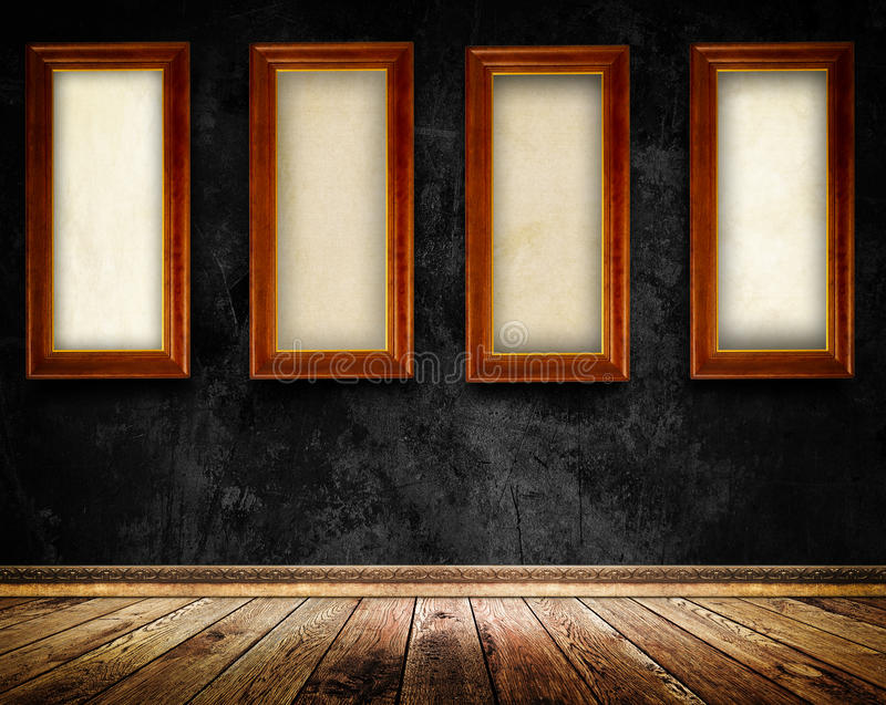 Wooden frames on old black wall. Old black concrete wall,four wooden frames with canvas and old wooden floor with decorative plinth stock photography