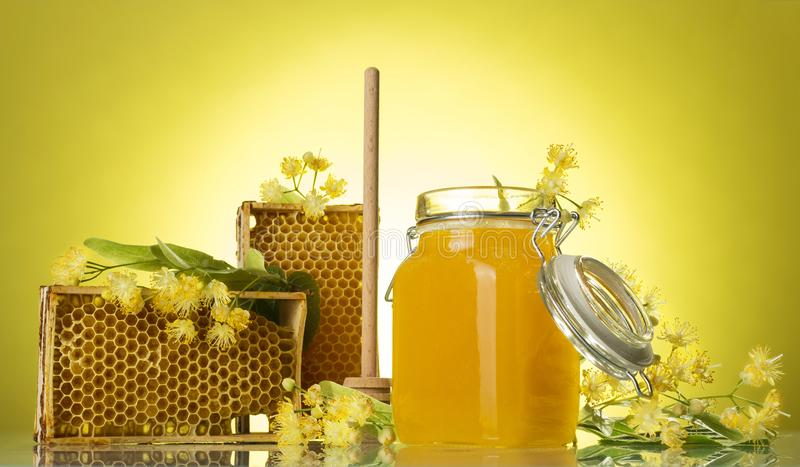 Wooden frames with wax honeycomb and honey in jar, on yellow background royalty free stock photo