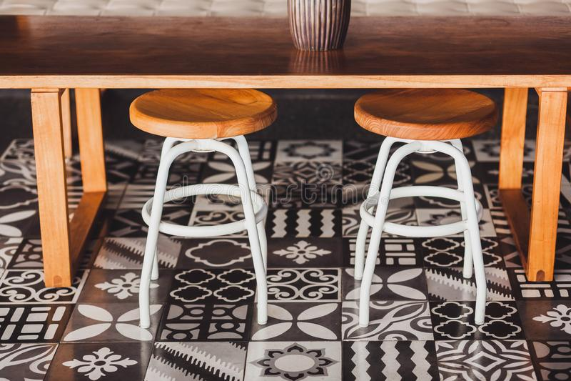 Wooden furniture in cafe, floor with ornament tile. Modern wooden furniture in cafe on floor with black and white ornament tile. Two chairs, table, sofa royalty free stock photos