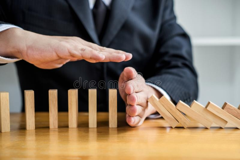 Wooden game strategy, Businessman hand stopping falling wooden d. Ominoes effect from continuous toppled or risk and protection, strategy and successful stock photo