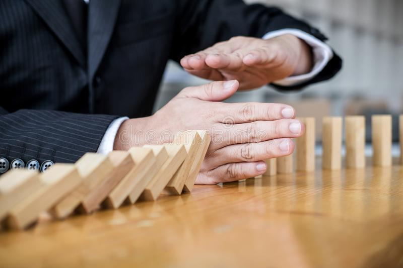 Wooden game strategy, Businessman hand stopping falling wooden d. Ominoes effect from continuous toppled or risk and protection, strategy and successful royalty free stock images