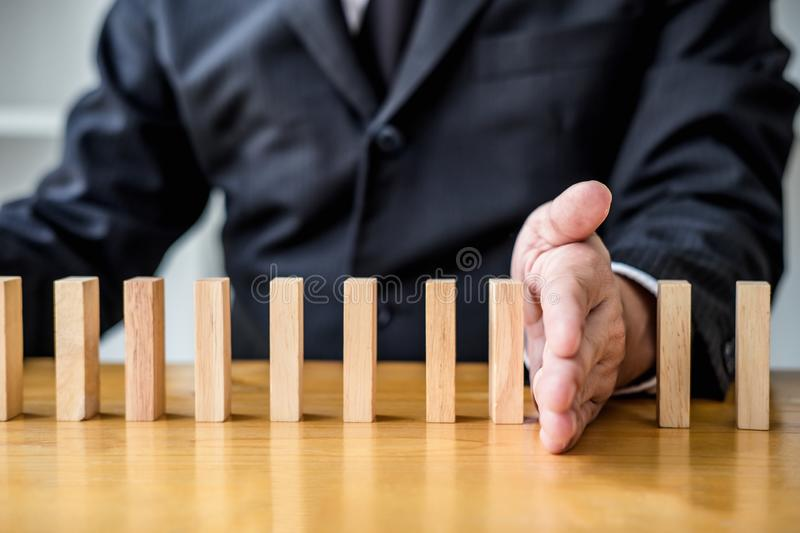 Wooden game strategy, Businessman hand stopping falling wooden d. Ominoes effect from continuous toppled or risk, strategy and successful intervention concept stock photography