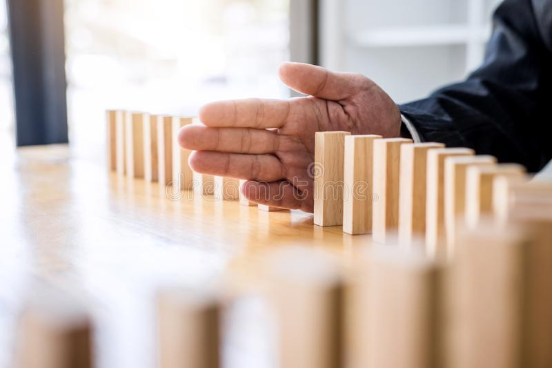Wooden game strategy, Businessman hand stopping falling wooden d. Ominoes effect from continuous toppled or risk, strategy and successful intervention concept royalty free stock image