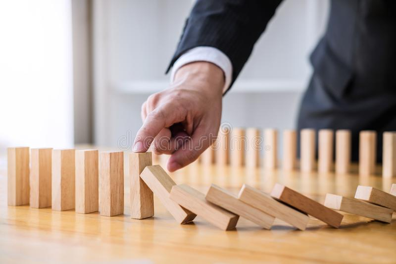 Wooden game strategy, Businessman hand stopping falling wooden d. Ominoes effect from continuous toppled or risk, strategy and successful intervention concept stock photo