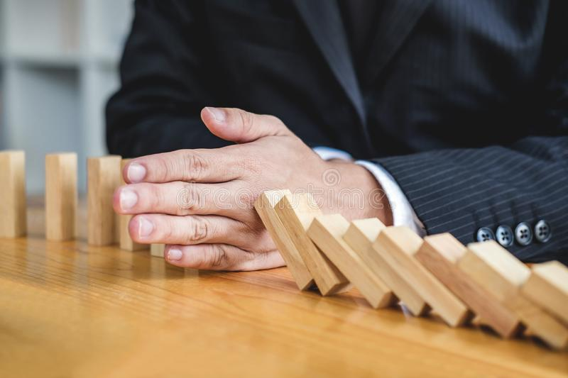 Wooden game strategy, Businessman hand stopping falling wooden d. Ominoes effect from continuous toppled or risk, strategy and successful intervention concept royalty free stock photography