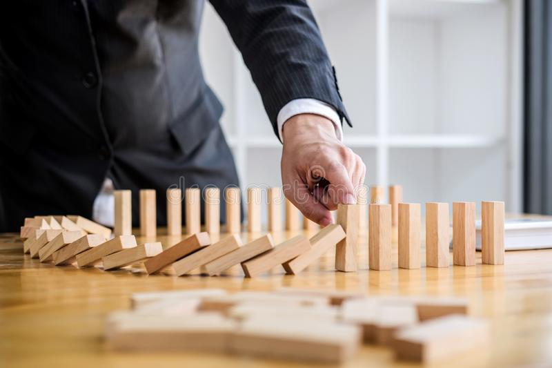 Wooden game strategy, Businessman hand stopping falling wooden d. Ominoes effect from continuous toppled or risk, strategy and successful intervention concept stock photos
