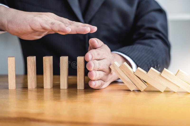 Wooden game strategy, Businessman hand stopping falling wooden dominoes effect from continuous toppled or risk and protection,. Strategy and successful royalty free stock images