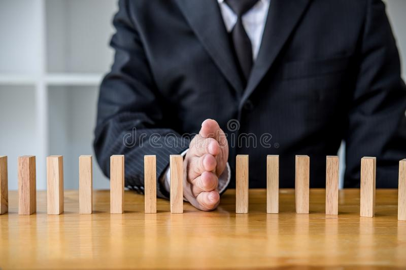 Wooden game strategy, Businessman hand stopping falling wooden dominoes effect from continuous toppled or risk, strategy and. Successful intervention concept stock images