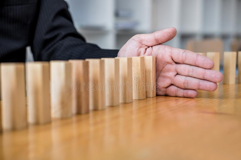 Wooden game strategy, Businessman hand stopping falling wooden dominoes effect from continuous toppled or risk, strategy and. Successful intervention concept royalty free stock photography