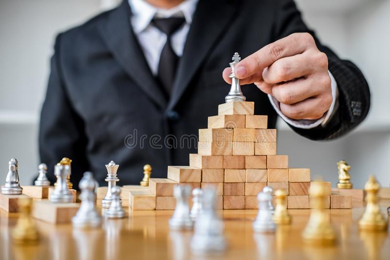 Wooden game of strategy, Hands of confident businessman playing. Chess game to development analysis new strategy plan, leader and teamwork concept for win and royalty free stock photography