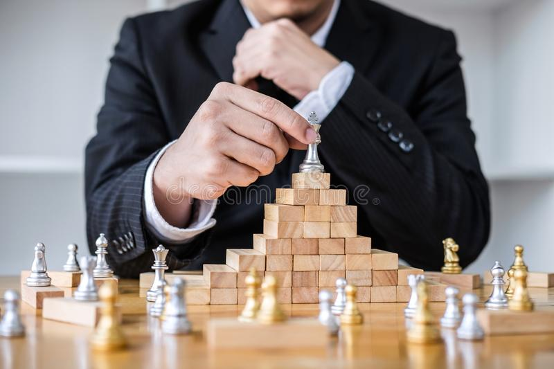 Wooden game of strategy, Hands of confident businessman playing. Chess game to development analysis new strategy plan, leader and teamwork concept for win and royalty free stock images