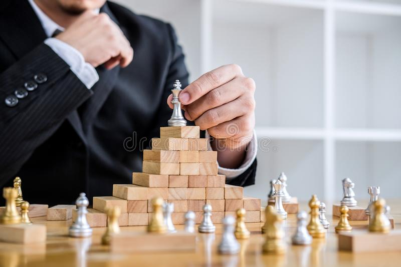 Wooden game of strategy, Hands of confident businessman playing. Chess game to development analysis new strategy plan, leader and teamwork concept for win and stock image