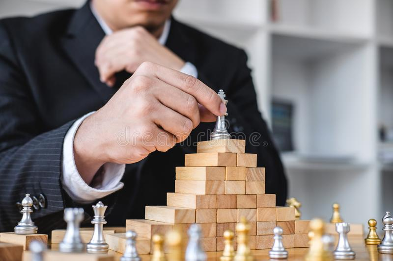 Wooden game of strategy, Hands of confident businessman playing. Chess game to development analysis new strategy plan, leader and teamwork concept for win and stock photos
